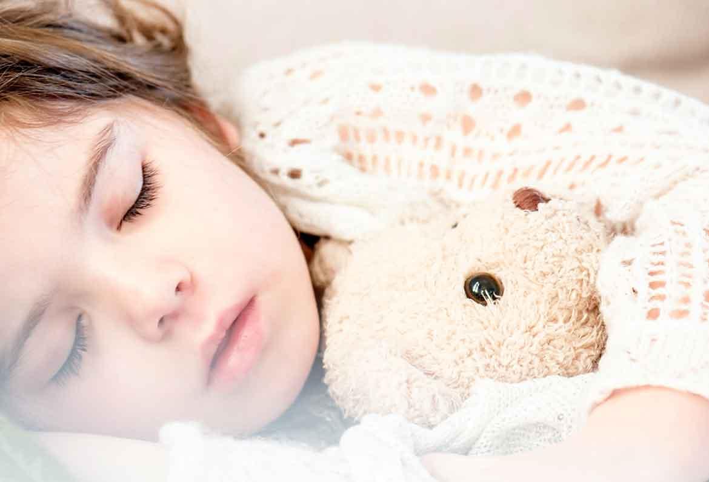 niña dormida con su oso de peluche