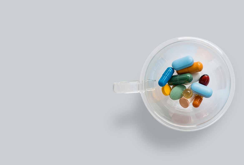 vaso con pastillas de diferentes formas y colores