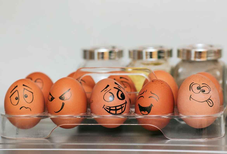 huevos en huevera con caras de emociones pintadas