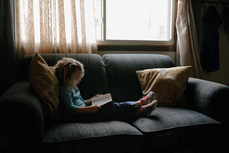 niña en el sofa leyendo