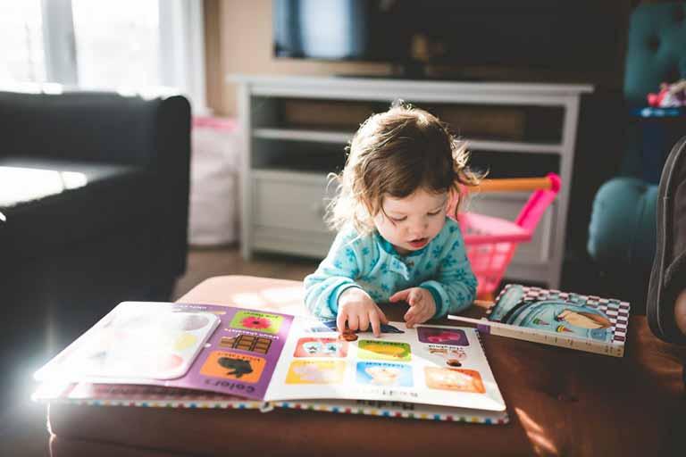niña pequeña con un libro de dibujos